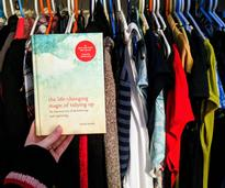 Marie Kondo book held up in front of closet