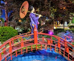 statue of Asian lady on bridge in mini golf course