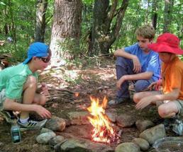 three kids at campfire