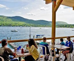 people on a restaurant deck overlooking lake george