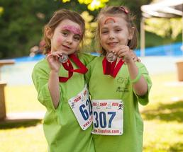 two girls holding up race medals