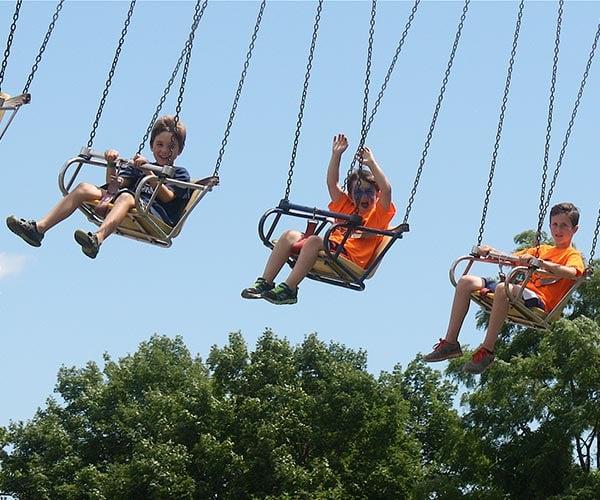 boys on a swing at the fair