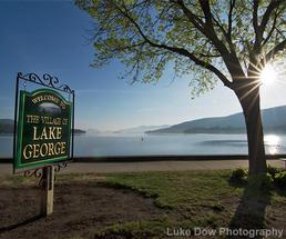 welcome to the village of lake george sign in front of the lake