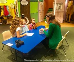 educator teaching three girls at the national museum of racing