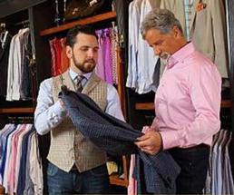 man examining shirt in men's clothing store