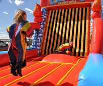 two kids jumping on an inflatable velcro wall