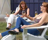 two women wine tasting and relaxing in chairs