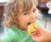 mother's hand feeding daughter a cheeseburger