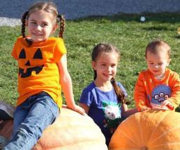 three kids on pumpkins