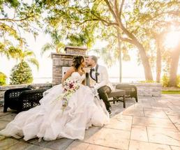 bride and groom kissing on a bench outdoors