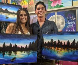 couple holding up paintings