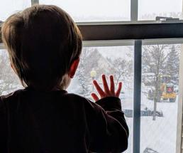 boy looking out the window after a snowstorm