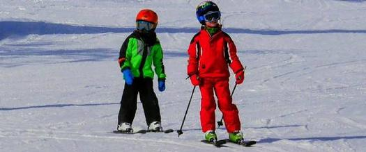 two kids downhill skiing
