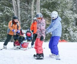 a kid learning how to snowboard at double h ranch