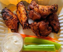 chicken wings, celery, carrots, and blue cheese dressing in a takeout container