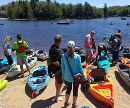 people and kayaks on shore