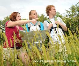 three people hiking through a field