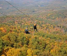 two people zipling over mountains with fall colors on the trees