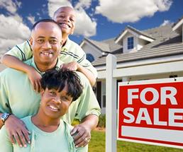 happy family next to house for sale sign
