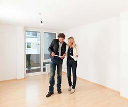 couple in an apartment with white walls, hardwood floors and sliding glass doors
