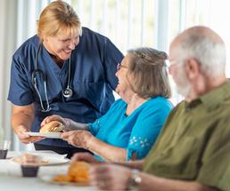 nurse serving a meal to two seniors at a nursing home