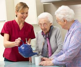 aide pouring tea for two older women