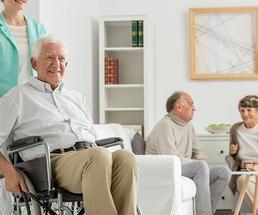 nurse pushing an older man in a wheelchair