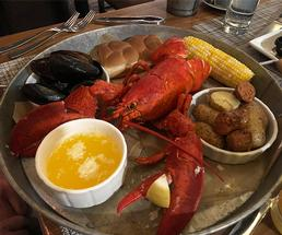 boiled lobster on a platter with bread, potatoes, corn, and butter