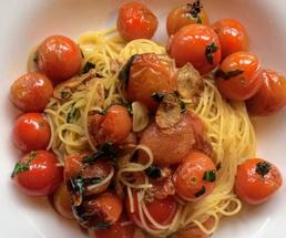cooked cherry tomatoes on pasta