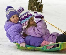 two little girls sledding