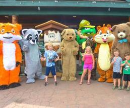 kids standing with costumed animal characters