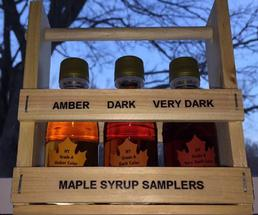 wooden case containing three maple syrup bottles