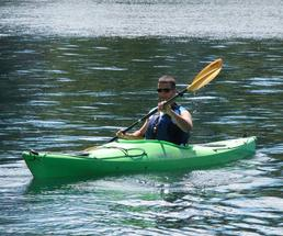 man paddling a green kayak