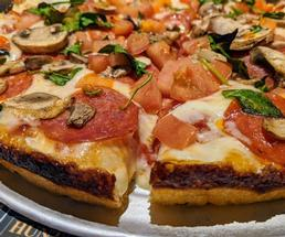 close up of pizza with mushrooms, spinach, pepperoni