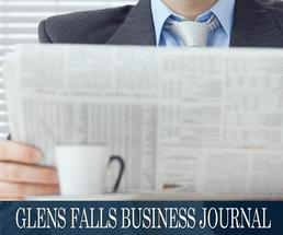 man reading a newspaper with the glens falls business journal header