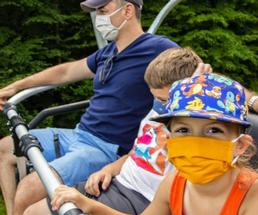 two kids and a parent on a ride wearing face masks