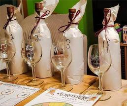 four wrapped bottles of wine with empty glasses