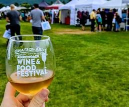 person holding an adirondack wine and food festival wine glass