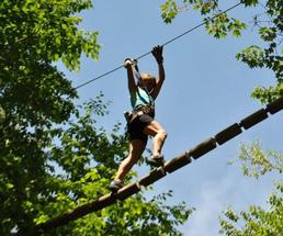 person crossing treetop obstacle