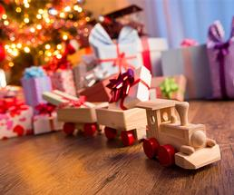 toy train with other gifts under a christmas tree