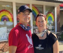 man and woman stand in front of rachel's cafe & spice co
