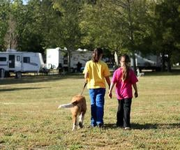 two girls walking through a campground with a dog on a leash