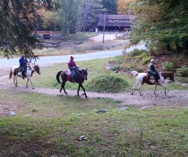 people horseback riding in the fall