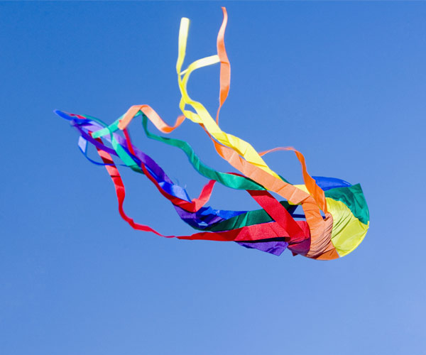 rainbow kite against a blue sky