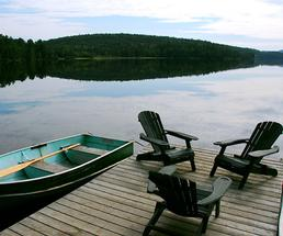 Canoe and Adirondack chairs on a dock