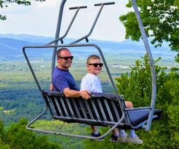 dad and kid on ski lift in summer