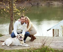Couple with dog on a dock at the lake