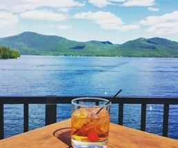 drink in a rocks glass on a table with lake george in the background