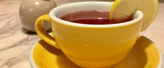 a red drink in a yellow cup with a lemon wedge