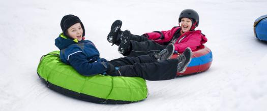 two kids snow tubing